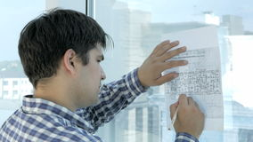 Engineer working on blueprint in a modern office. stock footage