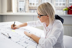 Engineer working on blueprint. In office Stock Photo