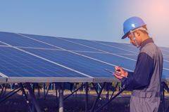 Engineer working on checking and maintenance structure and solar. Panel and find problem to operate at green energy solar power plant stock photo