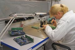 Engineer working with circuits. A woman engineer solders circuits sitting at a table stock photos