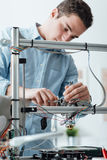 Engineer working on a 3D printer. Young efficient engineer working on a 3D printer and adjusting components stock photography
