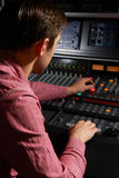 Engineer Working At Mixing Desk In Recording Studio Stock Photo