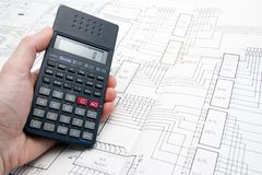 Engineer working on a project. With a calculator on his hand and an schematic on the table Stock Images