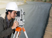 Engineer working with survey equipment theodolite with road unde Stock Photography