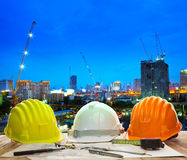 Engineer working table with hard hat plan and writing tool again. St beautiful lighting and urban building construction site use for land and city development stock photos