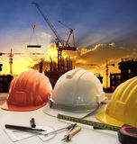 engineer working table plan, home model and writing tool equipment against building construction crane with evening dusky sky stock image
