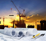 engineer working table plan, home model and writing tool equipment against building construction crane with evening dusky sky royalty free stock photos