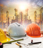 Engineer working table plan, and oil refinery plant in heavy pet Stock Image
