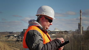 Engineer working with tablet PC near factory stock footage