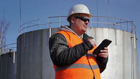 Engineer working with tablet PC near oil tank stock video footage