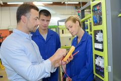 Engineer at workplace with apprentices in factory stock photography