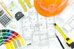 Engineer workplace with helmet, blueprint, and measuring tools Stock Photography