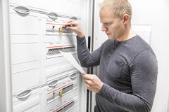 IT engineer works in large fuse cabinet Stock Image