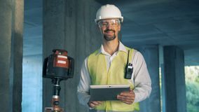 A worker types on a tablet and smiles at camera, close up. stock video footage