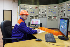 Engineer writes turbines parameters in log. On main control panel of gas compressor station Royalty Free Stock Photo
