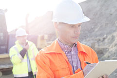 Engineer writing on clipboard at construction site with colleague in background Stock Photos