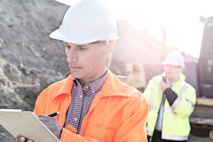 Engineer writing on clipboard at construction site with colleague in background Stock Photo