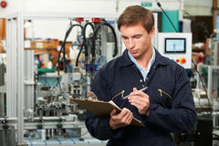 Engineer Writing On Clipboard In Factory. Engineer Writes On Clipboard In Factory Royalty Free Stock Photos