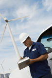 Engineer Writing On Clipboard At Wind Farm Royalty Free Stock Photos