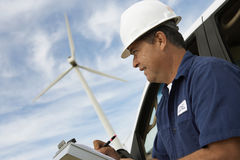 Engineer Writing On Clipboard At Wind Farm Royalty Free Stock Photo