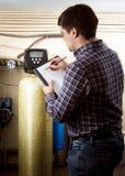 Engineer writing down meter reading on industrial counters. Young engineer writing down meter reading on industrial counters Royalty Free Stock Image
