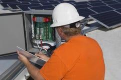 Engineer Writing Notes While Analyzing Electricity Box. Electrical engineer writing notes while analyzing electricity box at solar power plant stock image
