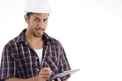 Engineer writing on pad and looking at camera Stock Photo