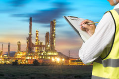 Engineer writing on the paper in front of the natural gas pipes. Stock Photography
