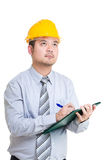 Engineer writing something on clipboard and looking up Stock Image