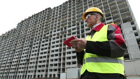 Engineer in yellow helmet stands with red smartphone near unfinished house. Worker inputs the data in his electronic device. Builder holding telephone and stock video footage