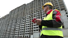 Engineer in yellow helmet stays with telephone near unfinished house. Builder in green vest holding telephone and looking around. Unfinished house behind him stock video