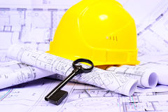 Engineering. Construction plan, blueprints with key and helmet Stock Images