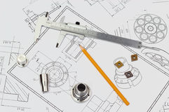 Engineering background. Analog caliper with pencil, parts and turning inserts CCMT type on drawings Royalty Free Stock Image