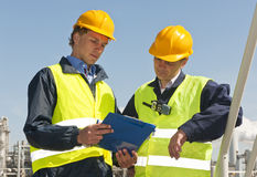 Engineering checklist. Two petrochemical engineers wearing safety vests and a hard top going over a checklist Royalty Free Stock Image