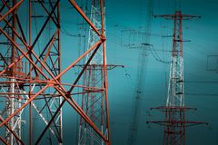 National Energy Grid system. Power pylons connecting the country. Red steel structures on deep blue sky stock photo