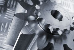 Engineering concept. Cogs, gears slanting towards right against patterned steel Royalty Free Stock Photos