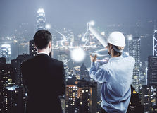 Engineering concept. Back view of insdustrial worker explaining something to businessman on illuminated night city background. Engineering concept stock image