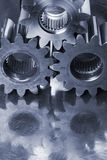 Engineering concept in bluish color. Three cogs, gears connecting against stainless steel stock photos