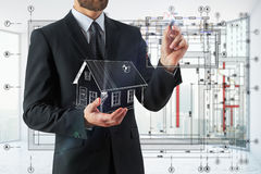 Engineering concept. Businessman holding abstract house model and drawing on blurry interior background. Engineering concept. 3D Rendering Royalty Free Stock Photography