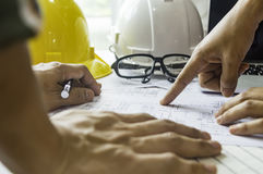 Engineering concept. Man of engineers hand point at a blueprint for construction on the table. Engineering concept Stock Photography