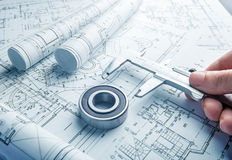 Engineering concept. Technology blueprints and bearing in hands Royalty Free Stock Photography