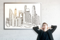 Engineering concept. Thoughtful businessman with city sketch in frame. Brick wall background. Engineering concept Royalty Free Stock Photos