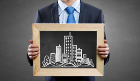 Engineering education. Unrecognizable businessman holding chalkboard with construction sketches stock image