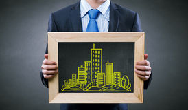 Engineering education. Unrecognizable businessman holding chalkboard with construction sketches stock images