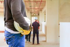 Engineering hand holding white safety hat interior  renovate house working construction site. In building with copy space add text Stock Image