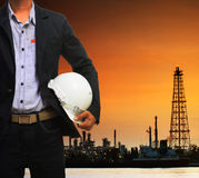 Engineering man and safety helmet standing against beautiful dus. Ky sky of oil refinery plant scene use for energy of fossil fuel and industry topic background Stock Photography