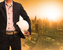 Engineering man and sun light behind urban construction backgrou Stock Photos