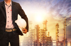 Engineering man with white safety helmet standing in front of oi. L refinery building structure in heavy petrochemical industry Royalty Free Stock Image