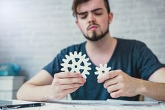 Engineering man working on blueprint for designing mechanical pa. Rts is adjusting a 3D printer`s components in office. Engineering tools and Business concept stock image