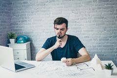 Engineering man working on blueprint for designing mechanical pa. Rts,he is having a bad headache, stress and overwork concept royalty free stock photo